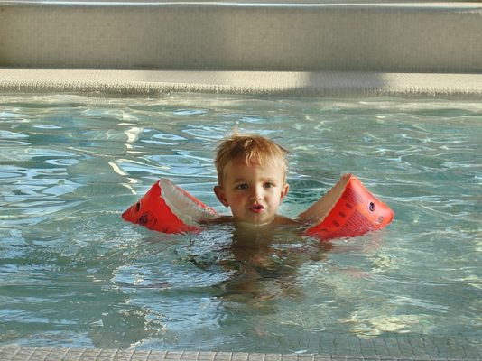 mall child with water wings in pool