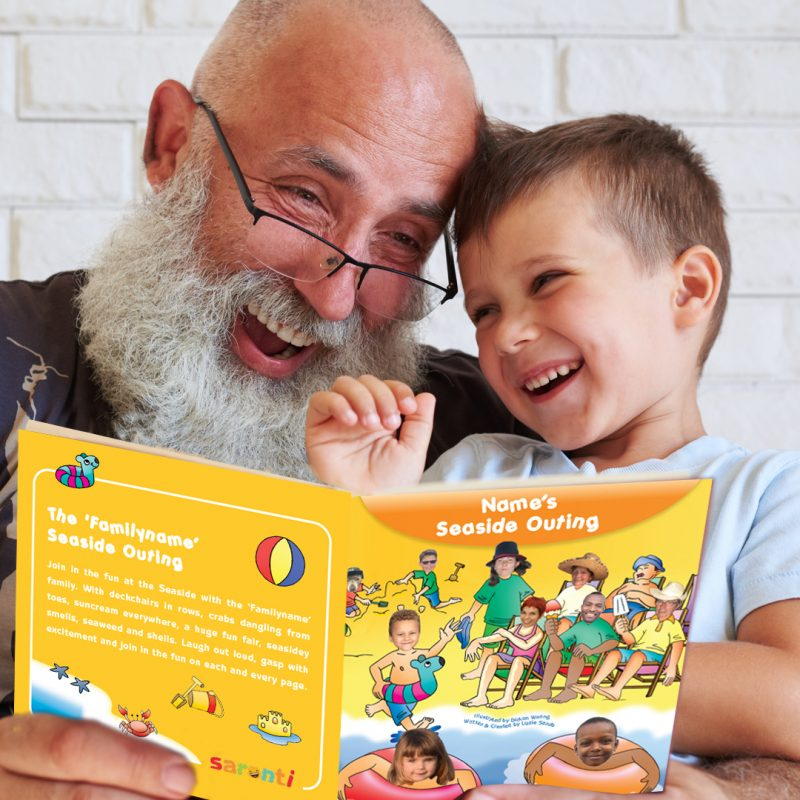 Grandfather and grandson reading book together laughing