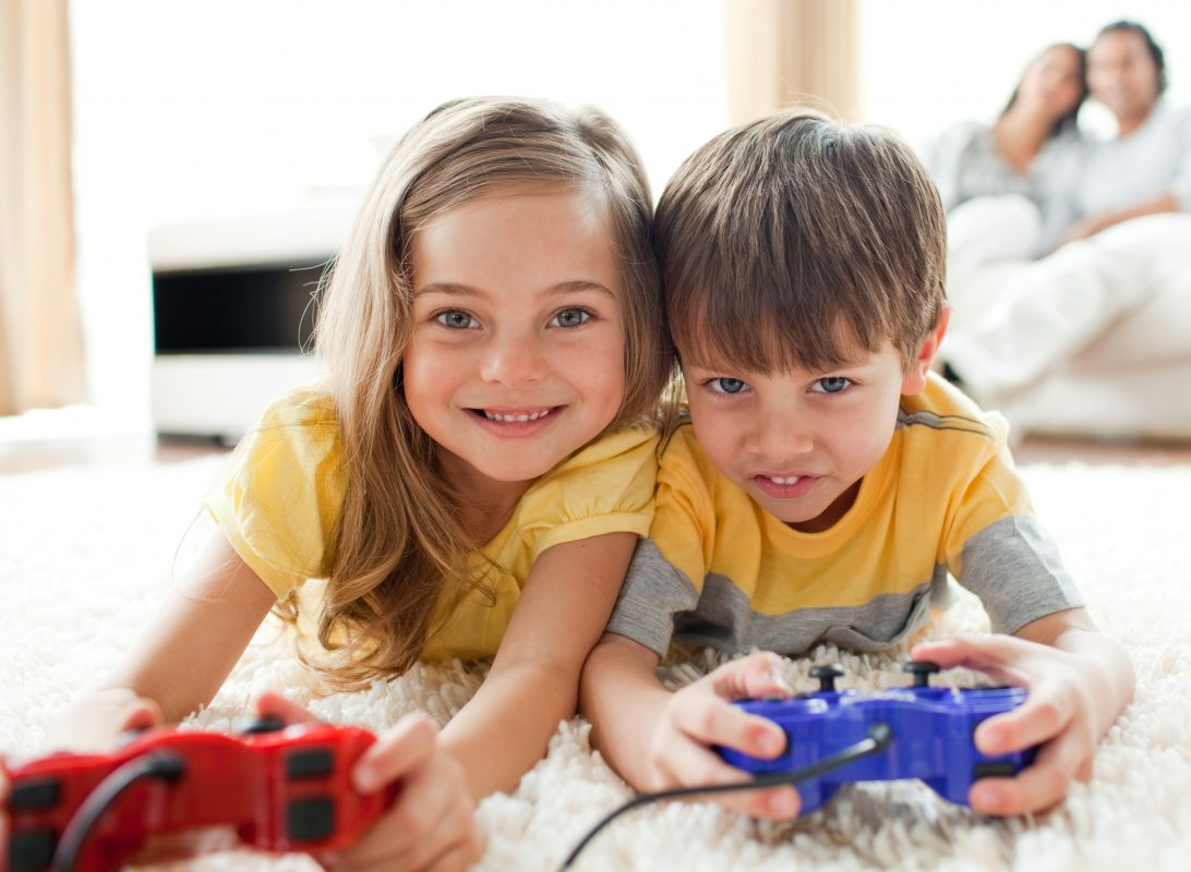 girl and boy playing on console smiling