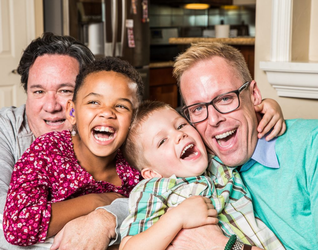 two dads and two children laughing