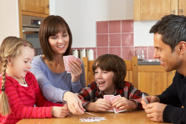 family playing cards at a table